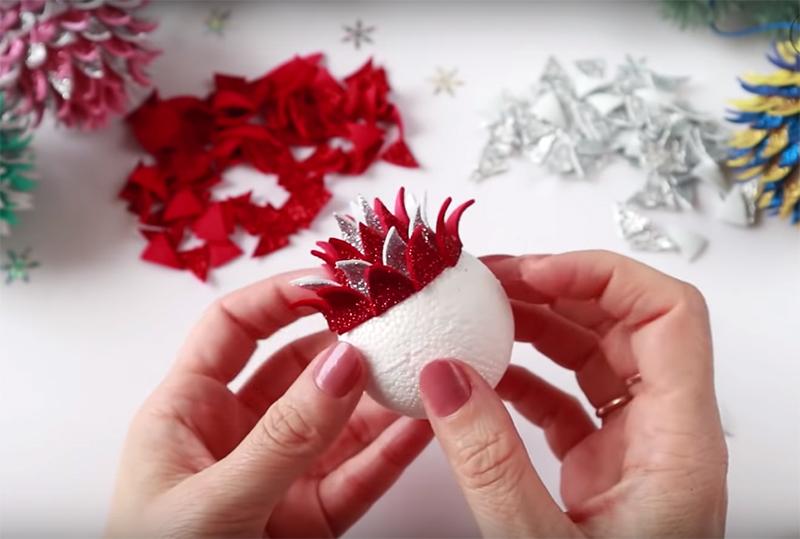 Чередуйте чешуйки разного цвета и добавляйте кольца одно за другим по всей поверхности пенопластового шарика. До «экватора» заготовки их количество будет увеличиваться, а потом уменьшаться