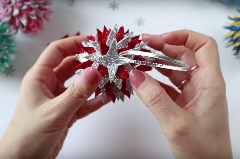 Сделайте в шарике небольшое отверстие, капните каплю клея и утопите узелок ленты в пенопласте. В глиттерной звёздочке сделайте отверстие и проденьте сквозь него петлю, а саму звёздочку закрепите на вершине шишки. Теперь место крепления петли совсем незаметно