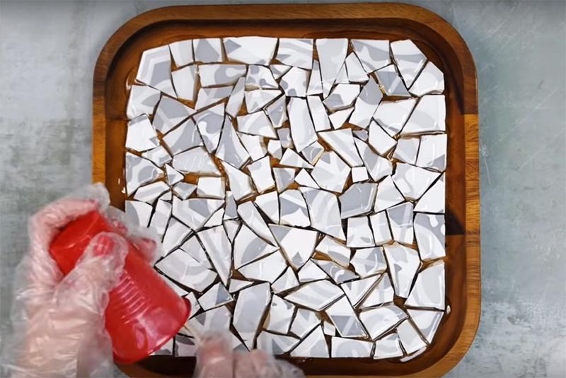 Наклейте, используя клеевой пистолет, все кусочки мозаики на основу, а потом залейте поверхность эпоксидной смолой так, чтобы она заполнила все углубления