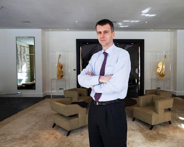 В гостиной установлены золотые виолончели за стеклянными витринами