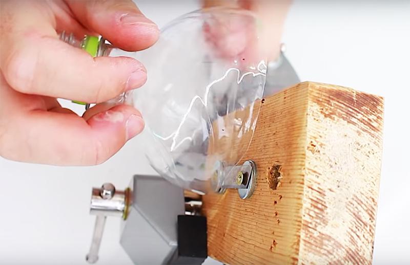 Чтобы разрезать бутылку на длинную и ровную нить, нужно сначала подрезать край ножницами, продеть его под лезвие и затем тянуть, прижимая край бутылки к доске