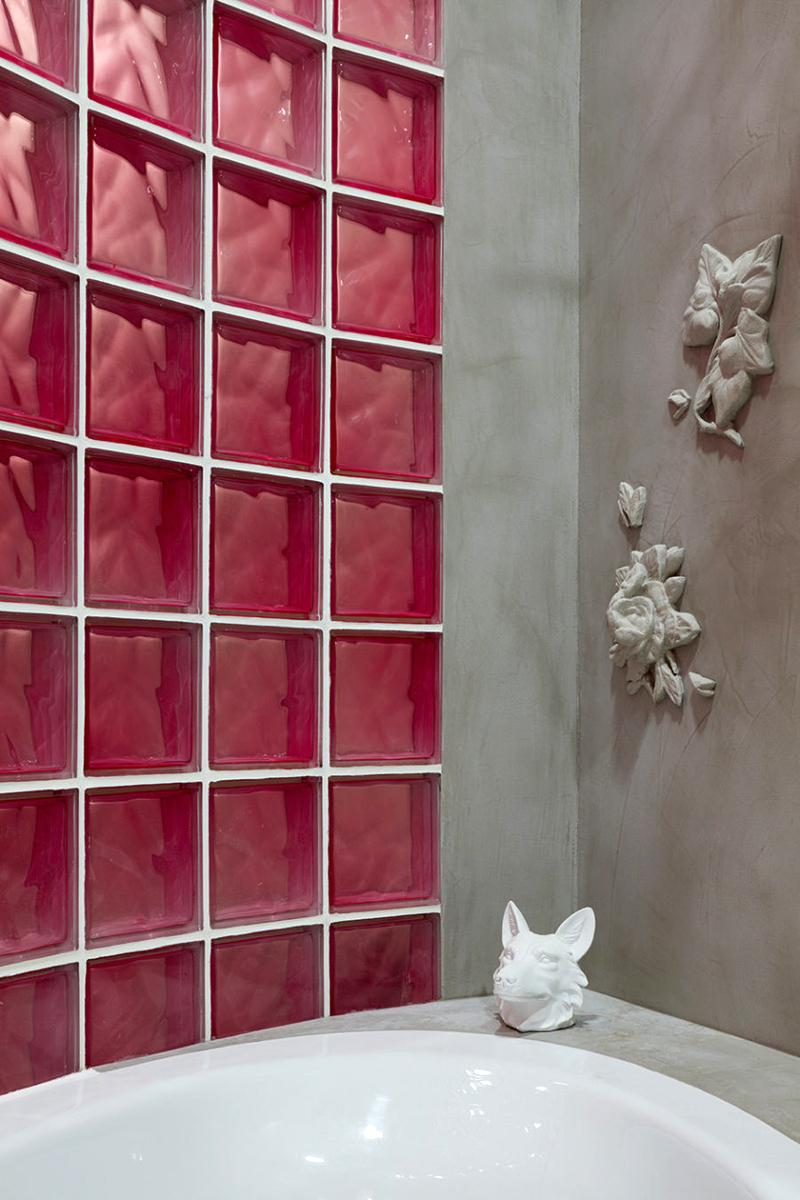 Бетонные стены ванной комнаты украшает несколько барельефов с цветочной композицией