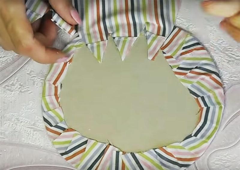 Вырежьте из картона круг такого диаметра, чтобы он помещался в банке, и оберните его тканью