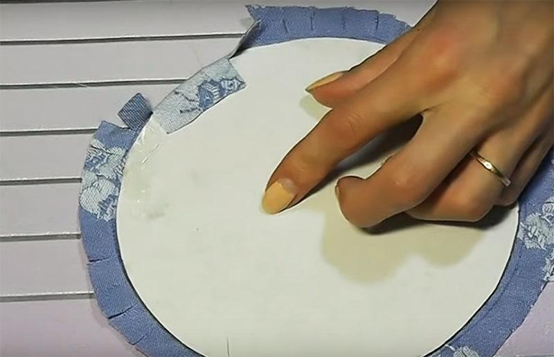 Сделайте 4 круга из картона такого размера, чтобы помещались в банке и обклейте их тканью. Один круг пойдёт на донышко банки снаружи, второй – изнутри. Два остальных нужно склеить между собой тканью наружу, чтобы получилась крышка шкатулки