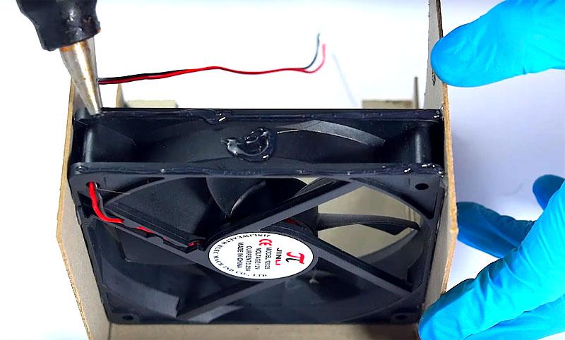 Соберите картонную коробку, приклеивая стенки прямо по периметру вентилятора клеевым пистолетом
