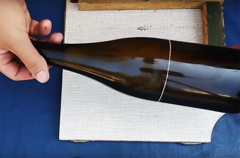 Просто приложите бутылку к доске так, чтобы донышко уперлось в деревянный уголок и, вращая её по оси, прочертите стеклорезом ровную линию