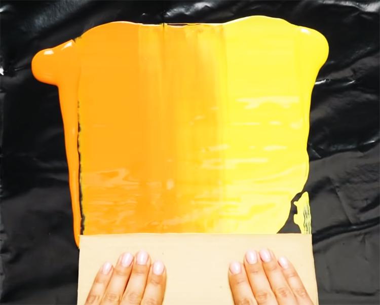 Шпателем или любым другим плоским предметом разровняйте краску на импровизированной палитре