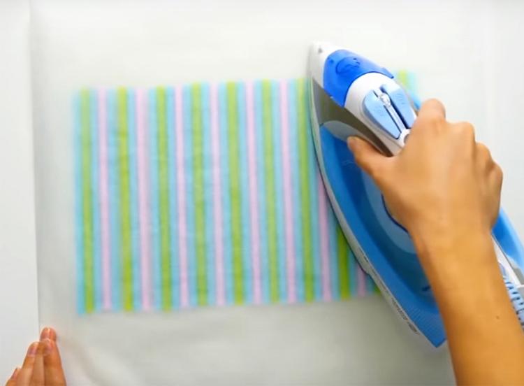 Накройте трубочки вторым листом бумаги и пройдитесь поверх горячим утюгом так, чтобы трубочки расплавились