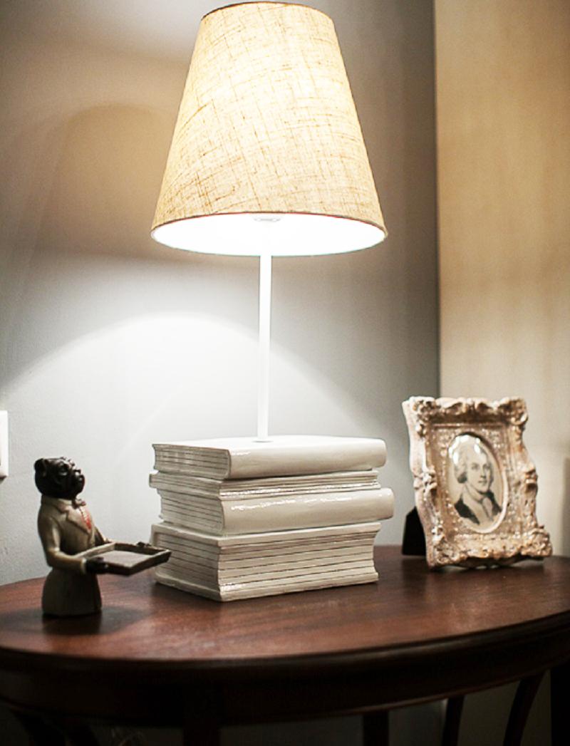 Столешницу круглого столика украшает необычная настольная ваза со льняным абажуром, установленная на подножке в виде книг