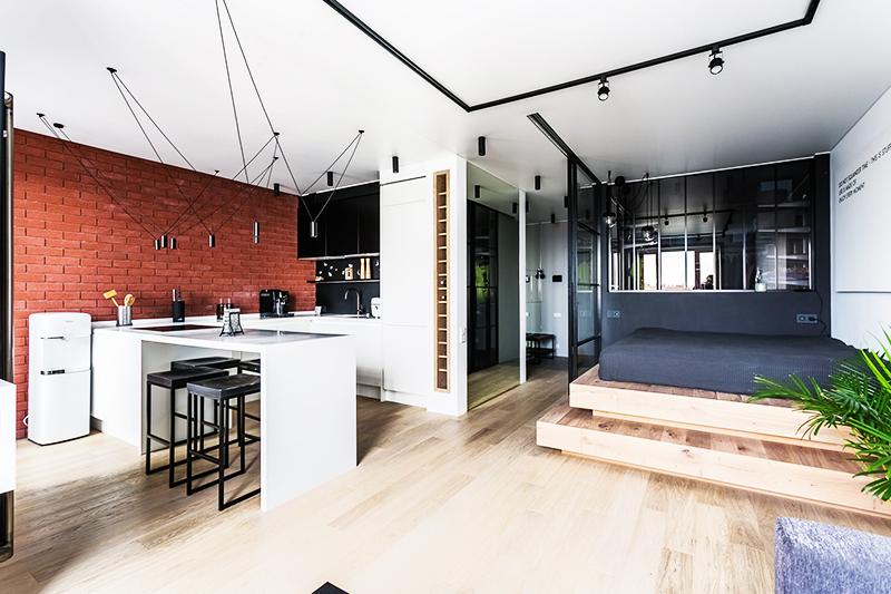 Установите небольшой подиум возле одной стены и разместите на нём кровать, отделив её от остальной части квартиры прозрачной перегородкой