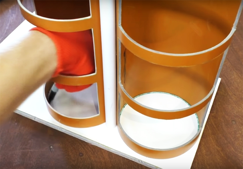 Чтобы точно разметить донышки для полок, поставьте заготовку на пластик и обведите маркером внутреннюю окружность
