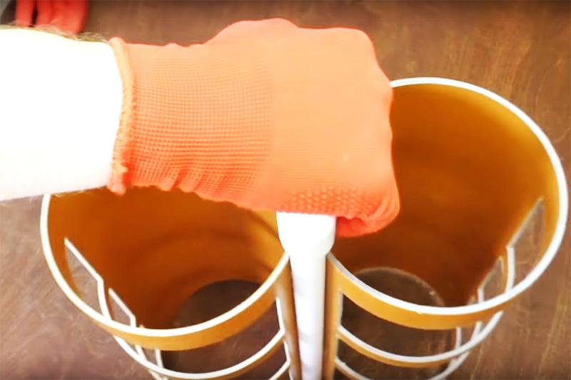 Два отрезка водопроводной трубы фиксируются на заготовке, а сверху они объединяются коротким отрезком, зафиксированным на сантехнических уголках