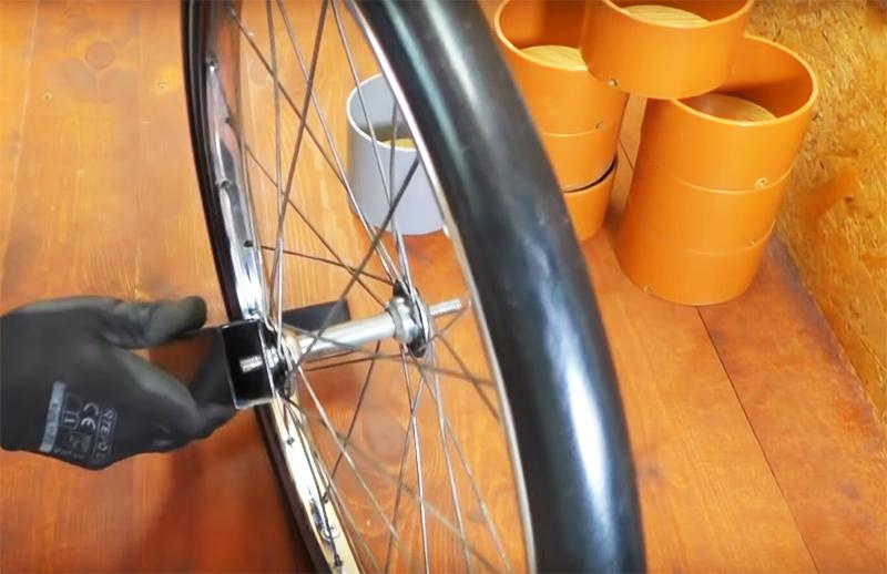 Зафиксируйте ось колеса на длинном конце держателя с помощью гайки