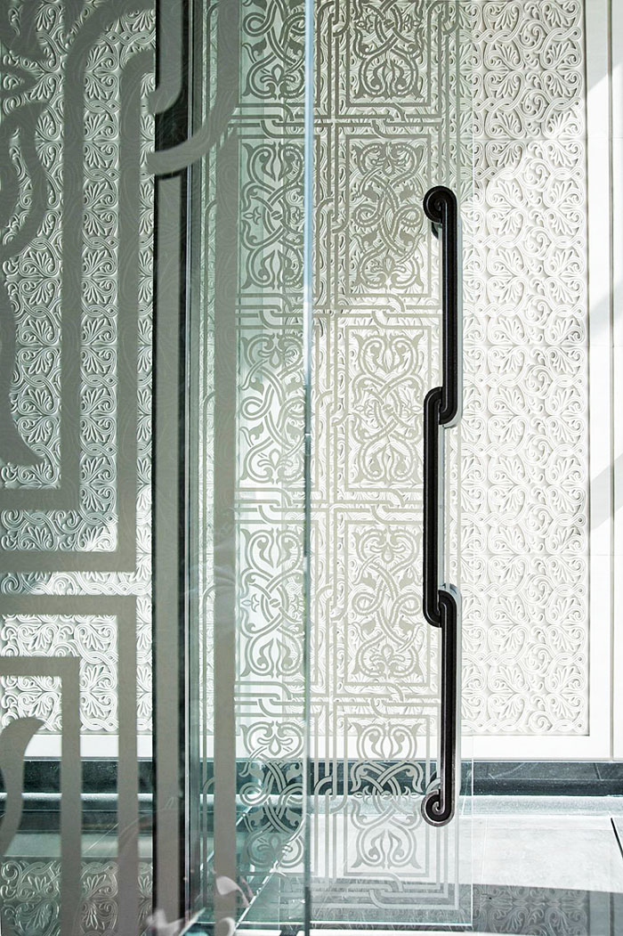 На стеклянные перегородки нанесена лазерная гравировка в азиатском стиле