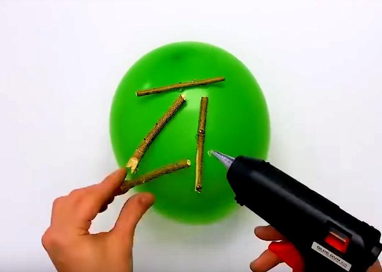 Приготовьте палочки из веток длиной примерно 10-12 см и закрепите их на шарике горячим клеем в разном положении