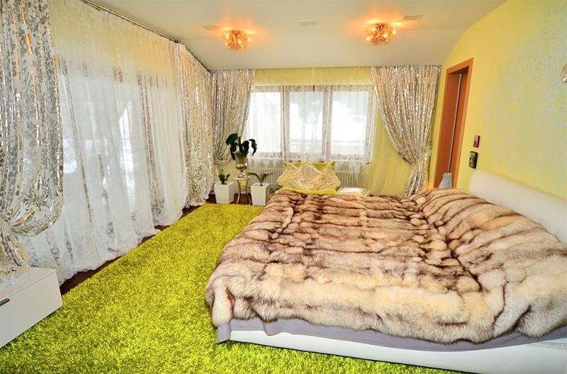Окна задрапированы белоснежным тюлем и роскошными шторами с цветочным серебряно-золотым принтом