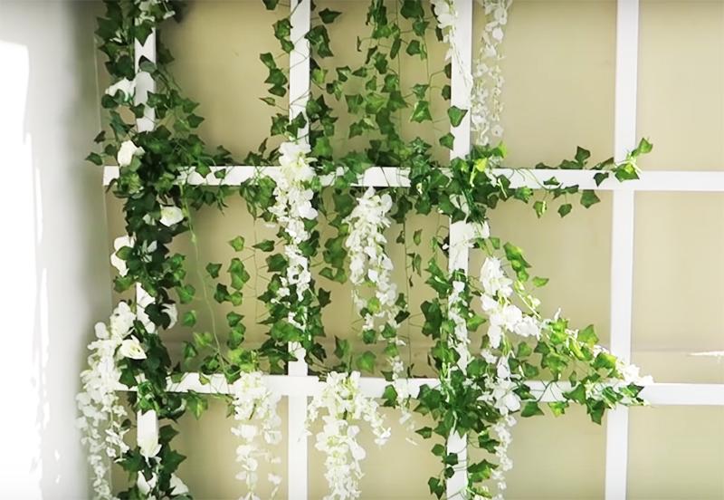 Если выбор пал на искусственные цветы – шикарно будет смотреться имитация глицинии с её цветочными гроздьями. Кстати, решётку совсем не обязательно прикручивать к стене – достаточно её просто прислонить и слегка зафиксировать снизу, чтобы случайно не поехала