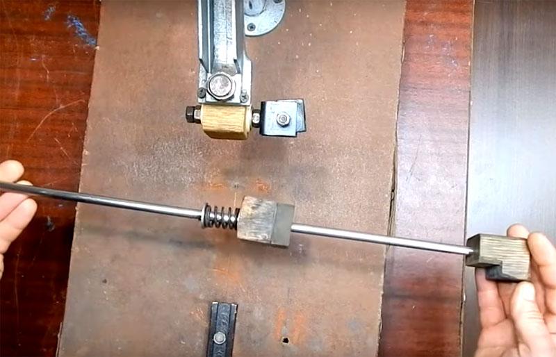 Вам потребуется спица с механизмом крепления камня. Фиксация будет за счёт двух деталей из дерева с выемками под камень. Одна из них свободно «ходит» по спице и при необходимости фиксируется за счёт пружины