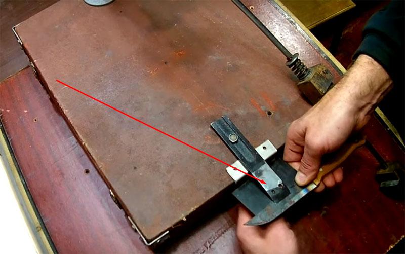 Нож фиксируется на подставке, которой является чемоданчик от фотоувеличителя. Для крепления на край короба нужно прикрутить детали: верхнюю – это полоска металла, зафиксированная в неподвижном положении, и нижнюю – пластинку, которая прижимает нож и может сдвигаться