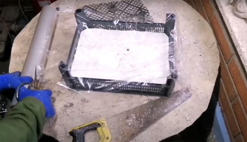Для лёгкого извлечения готовой плитки из формы нужно внутреннюю часть ящика проложить рулонной плёнкой. Она потом легко отделяется от готовой плитки