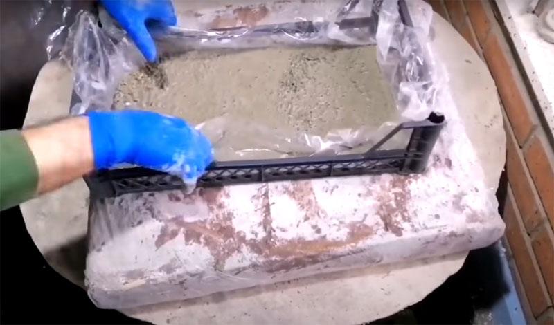 Заполните форму, равномерно распределите её по всему пространству и обязательно слегка встряхните ящик, чтобы вышли пузырьки воздуха, остатки которых могут неблагоприятно влиять на прочность будущей плитки. После нанесите второй слой раствора, изготовленный из цемента и песка в пропорции 1/2, и тщательно разгладьте поверхность