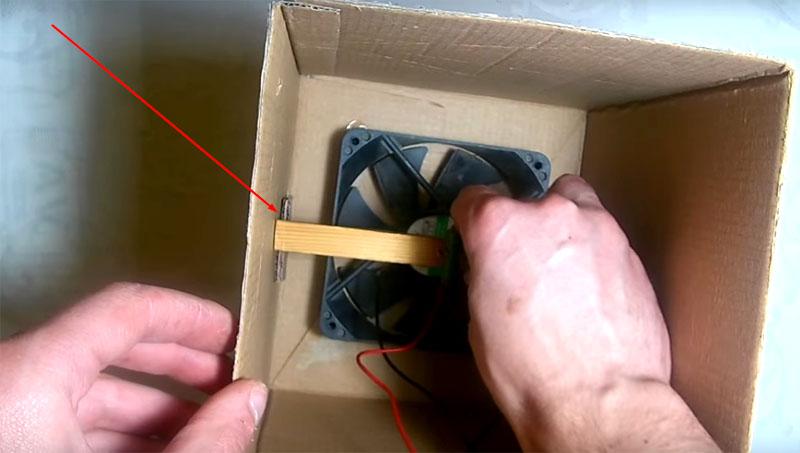 Приклейте кусочки картона на стенки коробки и поставьте на них планку. Добавьте клей прямо поверх этого соединения для надёжности