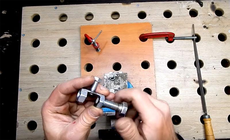 С боковых сторон импровизированной струбцины вкручиваются большие гайки. На них также нужно приклеить прокладки