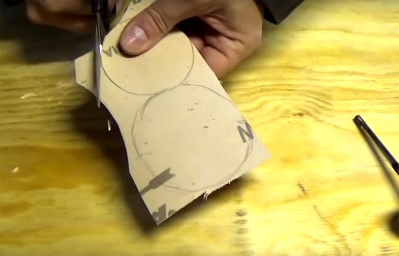 Вам нужно вымерять расстояние от края до края болванки и вырезать наждачную бумагу по кругу с соответствующим замерам диаметром