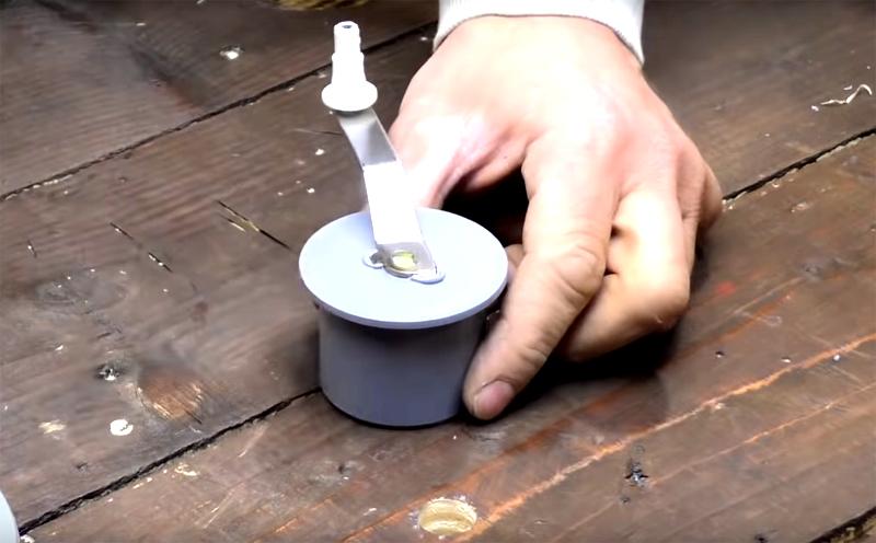 Последний шаг в подготовке деталей – это ручка для вращения катушки. Её фиксируют на заглушке для трубы меньшего диаметра с помощью самореза. Найти такую ручку вам будет нетрудно, но при желании вы можете сделать её и самостоятельно из подручных материалов, например из зубной щётки и пробки от шампанского