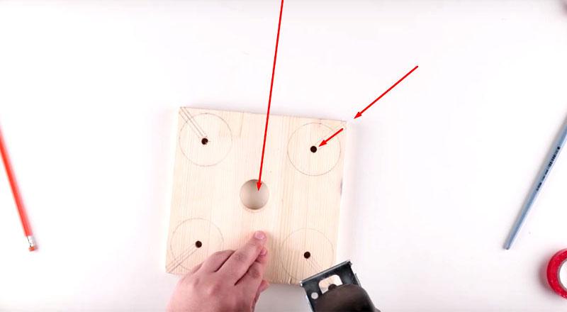 По центру корончатым сверлом нужно сделать отверстие такого диаметра, чтобы свободно проходило горлышко бутылки. А по краям следует выполнить запилы в местах, указанных стрелками