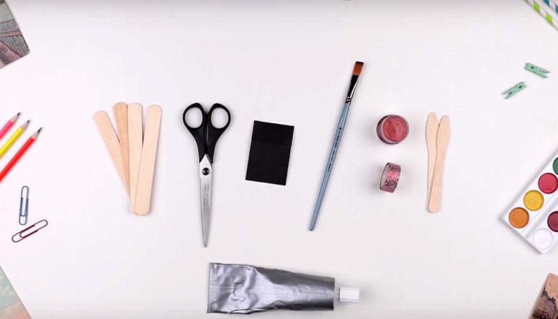 Для изготовления такой доски вам потребуются палочки для мороженого, акриловая краска, декоративный скотч, клей и пара магнитов или кусочки магнитной ленты
