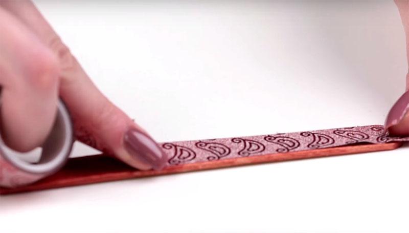 Окрасьте палочки в подходящий тон, когда краска высохнет, на одну сторону наклейте декоративный скотч