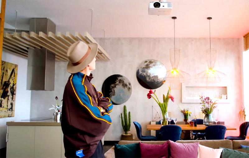 Над диваном закрепили проектор, который демонстрирует фильмы на установленный над лестницей экран