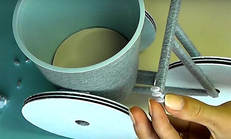 Для большей устойчивости приклейте кашпо на ось тележки — и конструкция готова. Вы можете поставить в неё вазу или посадить живой цветок