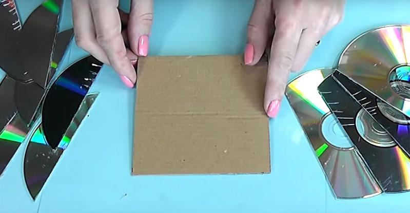Приготовьте кусок картона шириной, равной диаметру диска. Диски обрежьте так, чтобы получилось несколько полукругов, а ширина среза равнялась стороне квадрата