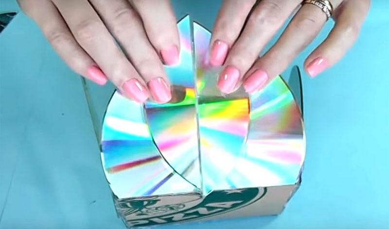 Обрезанные части дисков расположите с наружных сторон коробки, как лепестки. Они легко приклеятся горячим клеем