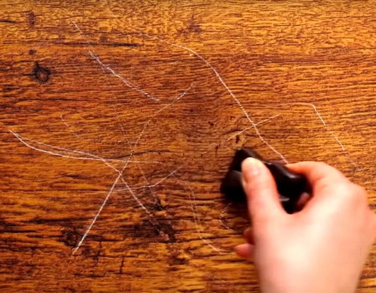 Отломите кусочек плитки и, слегка нажимая, натрите шоколадом царапины так, чтобы он заполнил все борозды