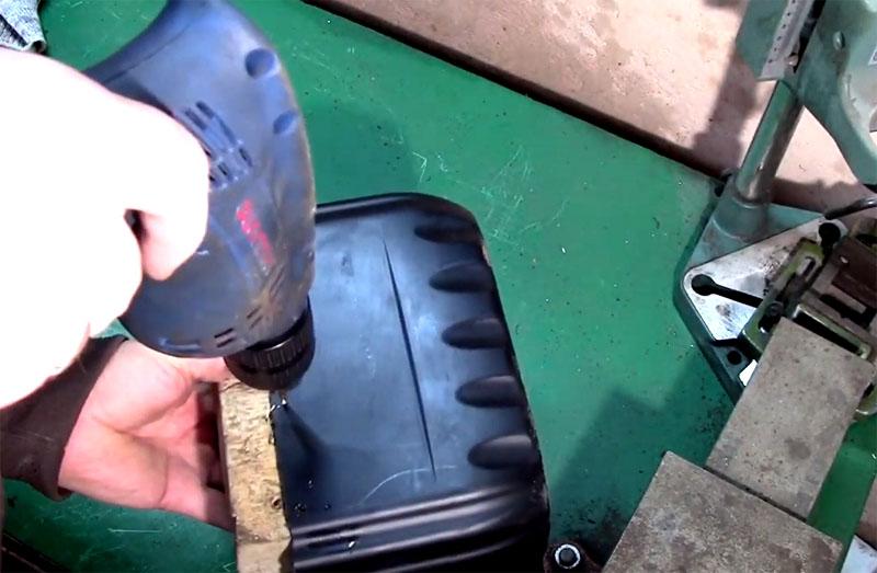 Чтобы соединить крышку и основную ёмкость канистры вместе петлёй, нужно отметить места крепления и просверлить отверстия под болты. Чтобы мягкий пластик не поддавался под давлением сверла, подложите что-то твёрдое под борт