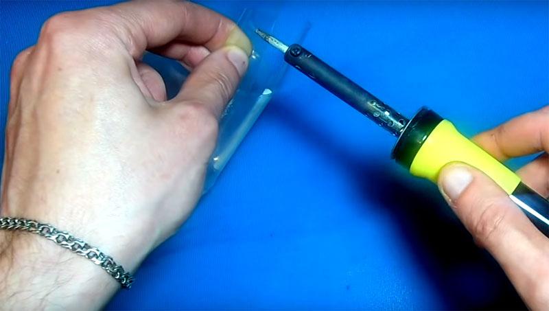 Отступите от края каждого лепестка примерно сантиметр и сделайте паяльником отверстие по центру. Если нет под рукой паяльника – нагрейте на плите обычную вязальную спицу