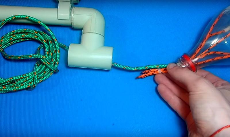 Возьмите длинную верёвку, проденьте её через отверстие тройника и скрепите с пучком верёвочек из бутылки такой же стяжкой. Обрежьте все лишние концы стяжки, чтобы они не мешались
