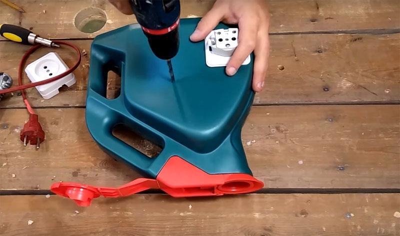 Для крепления розетки в стенке канистры нужно сделать сквозные отверстия, ещё необходимо будет приготовить пару отверстий под контакты