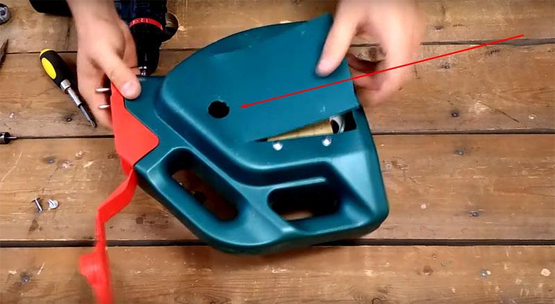 В верхней части канистры нужно будет сделать отверстие, чтобы можно было управлять кнопкой для скручивания провода. Отверстие должно быть достаточно большим, чтобы в него свободно проходил палец