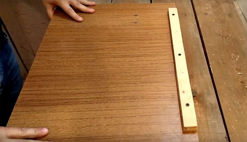 Уложите его на свой рабочий стол так, чтобы нижняя планка упёрлась в край стола