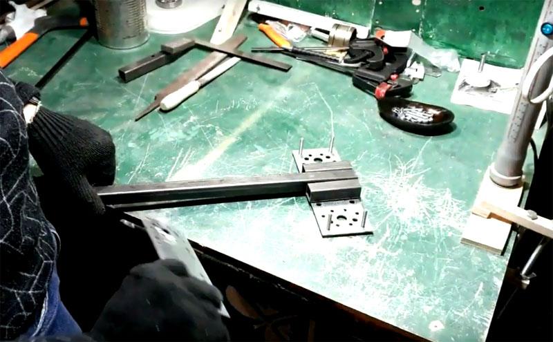 Конструкция стойки такова, что рукав с дрелью должен двигаться по направляющей вверх и вниз. Для этого отпилите два куска профильной трубы длиной 10 см и закрепите их на пластине так, чтобы они плотно прилегали к основной направляющей. Саму же направляющую на пластине не фиксируйте