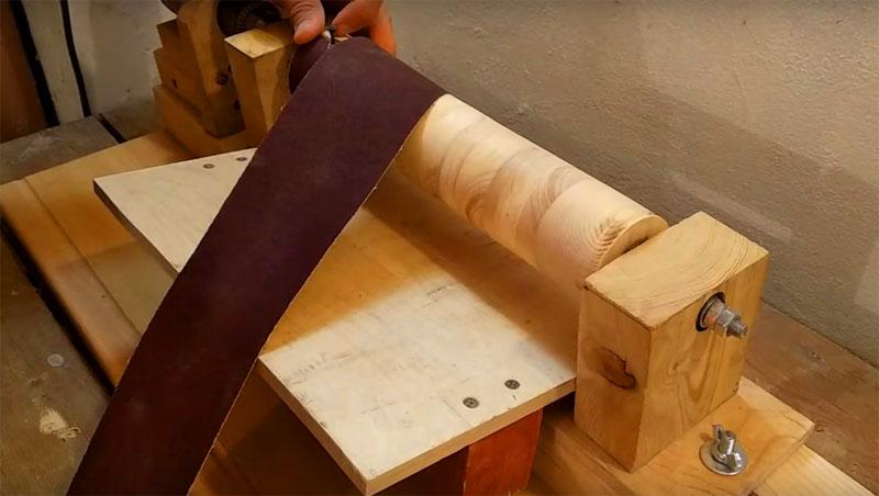 Для фиксации ленты наждачной бумаги сначала заведите её край в прорезь на барабане, прикрутите небольшим саморезом, а потом оберните барабан по спирали и повторите процедуру на другом конце