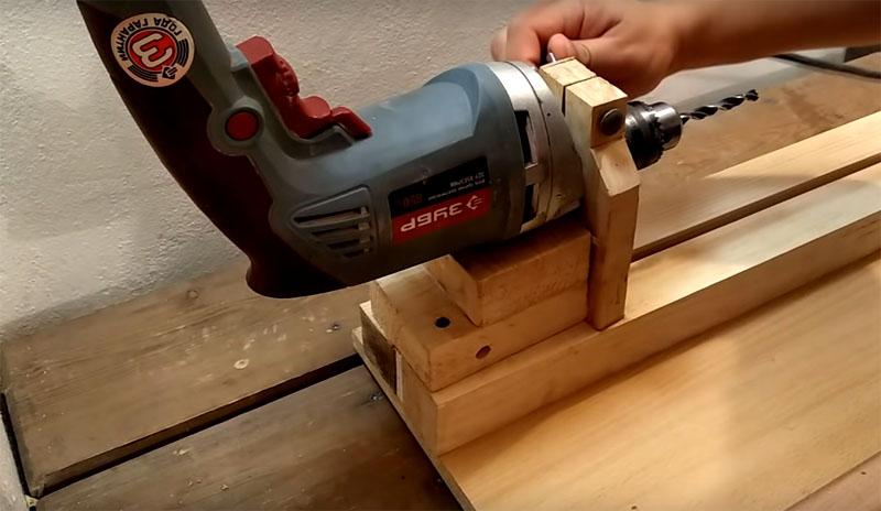 Дрель ставится на станке ручкой вверх, патрон помещается в деталь с прорезью. Теперь можно включить инструмент и зафиксировать кнопку включения