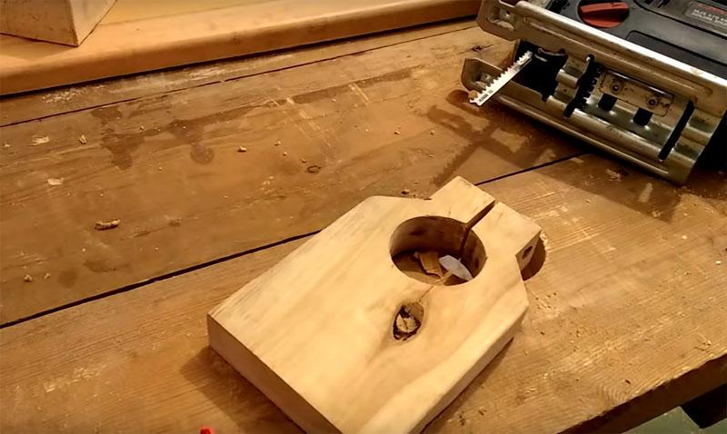 Чтобы закрепить дрель, нужно из обрезка доски сделать вот такую деталь с круглой прорезью. Обратите внимание: вверху отверстия сделан сквозной пропил. Само отверстие должно соответствовать диаметру патрона дрели