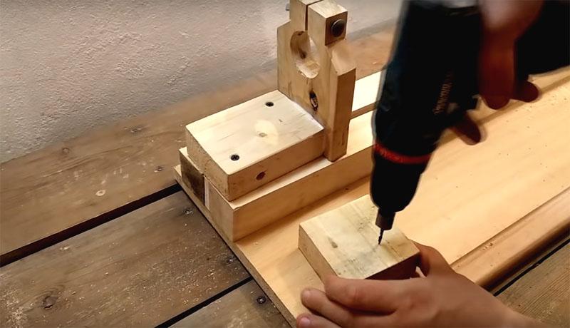 Деталь с прорезью устанавливается вертикально на полозьях из бруса. А к ней строится «лесенка» из обрезков доски по форме дрели