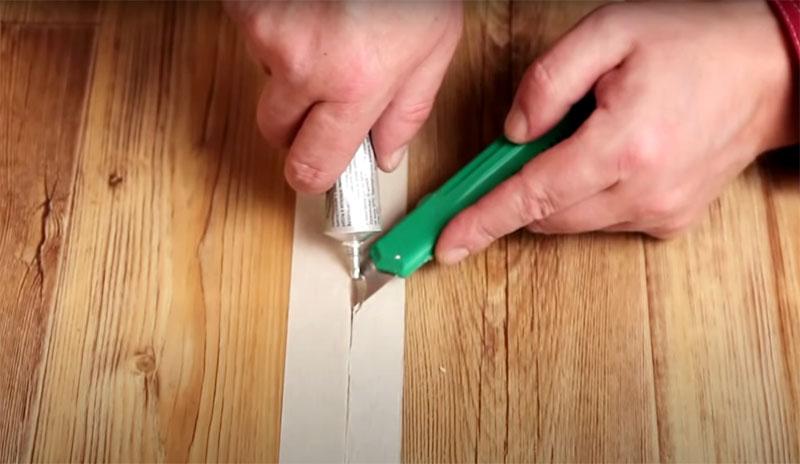 Подденьте тонким лезвием край линолеума и начинайте движение вдоль разреза, одновременно добавляя клей на место среза