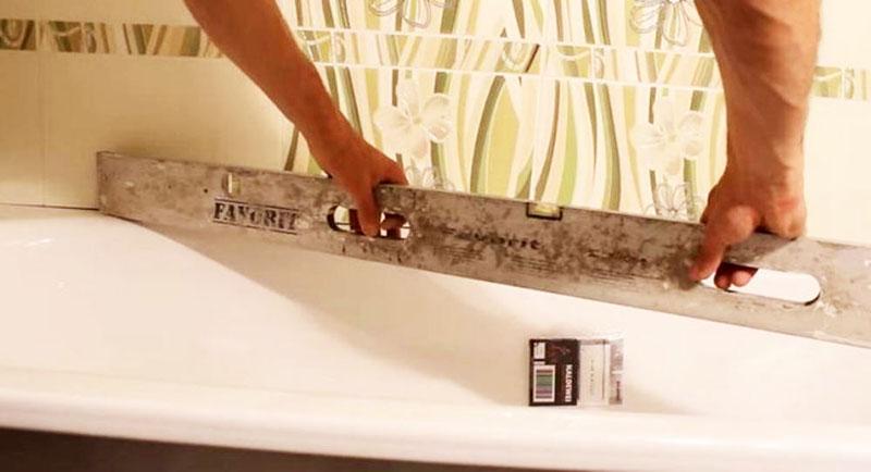 Выставление ванны при помощи строительного уровня и регулировочных болтов